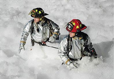 Firefighters srrounded by firefighting foam