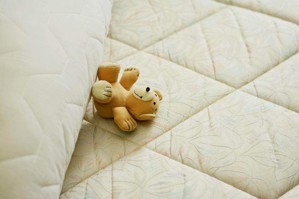 Mattress witha teddy bear on it