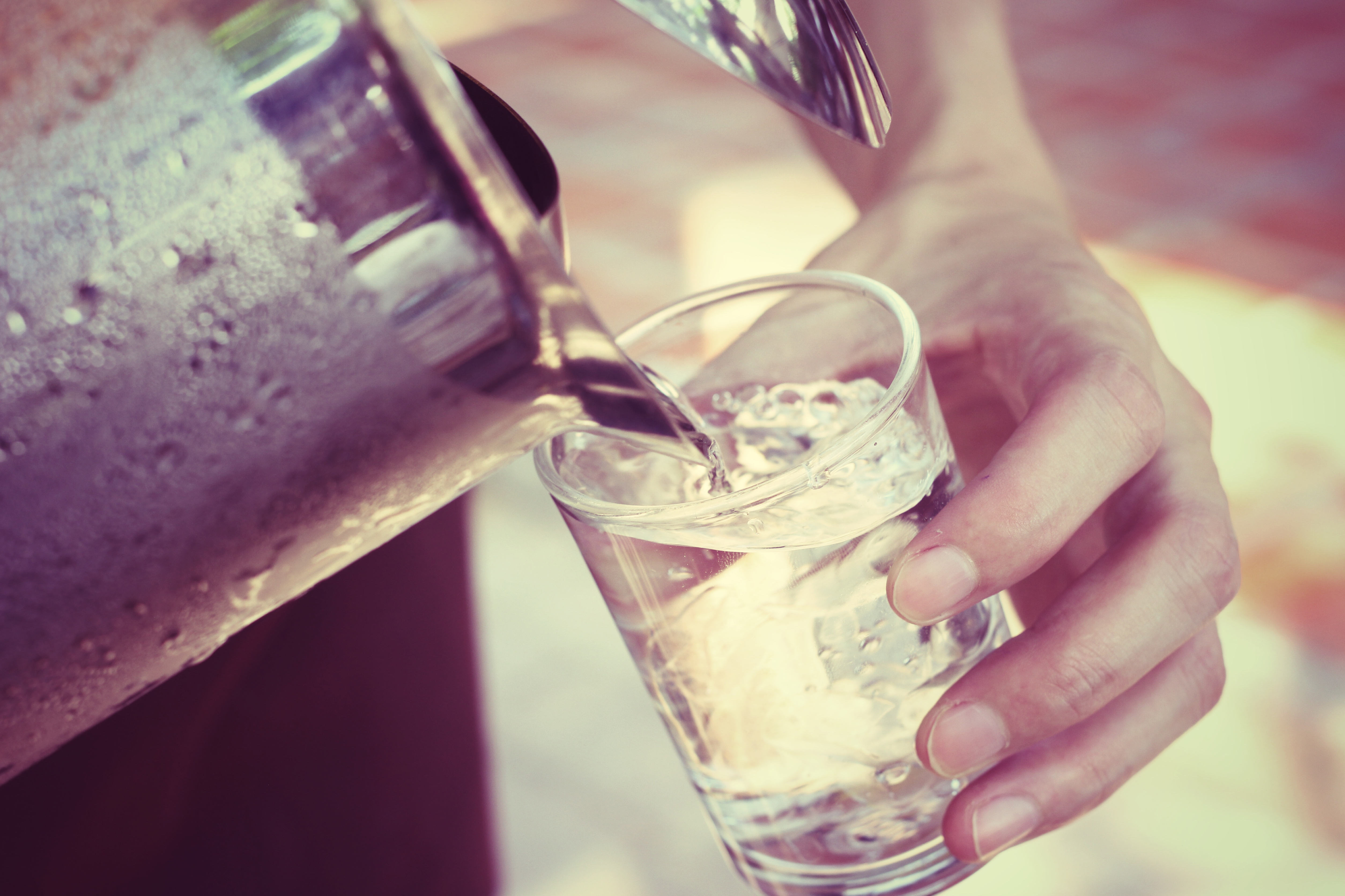 Pouring water from a pitcher into a glass. Photo credit: successo images / Shutterstock