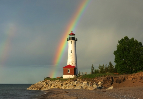 A lighthouse with a rainbow