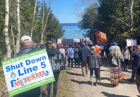 Crowd marching on Lake Michigan with Shut Down Line 5 Signs