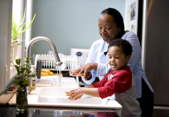 Parent and child at kitchen sink